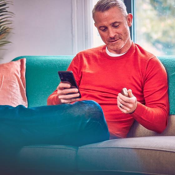 Мужчина с IQOS в одной руке и телефоном в другой рассматривает инструкцию